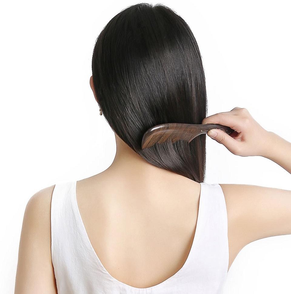Деревянная расческа для волос XinZhi Ebony в руках пользователя