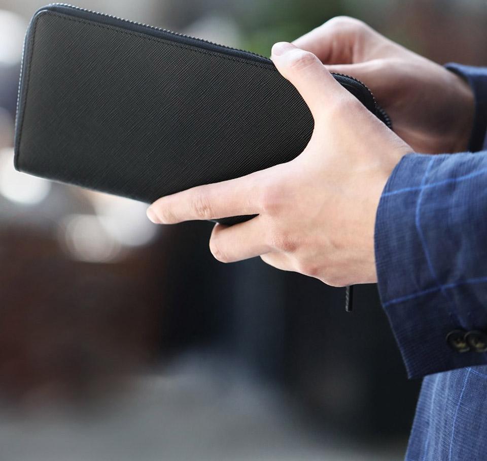 Бумажник кожаный RunMi 90 Points Long Wallet в руках мужчины